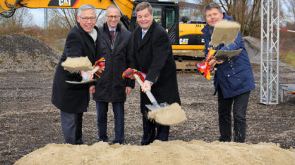 Politiker beim Spatenanstich, werfen Sand in Richtung Kamera