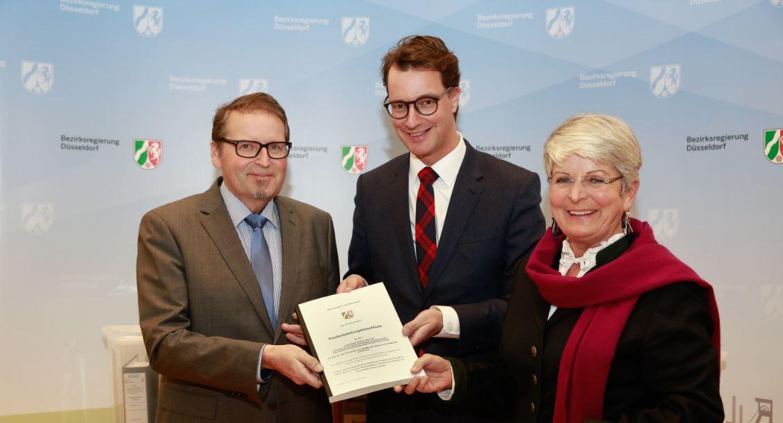 NRW-verkehrsminister Wüst und Regierungspräsidentin Rademacher überreichen den Beschluss