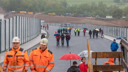 Menschen mit Regenschirmen laufen auf der Brücke