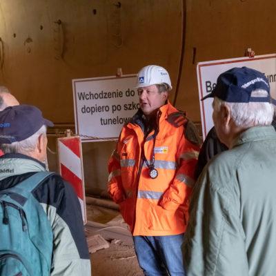 Mitarbeiter mit Helm spricht zu Besuchern im Tunnel