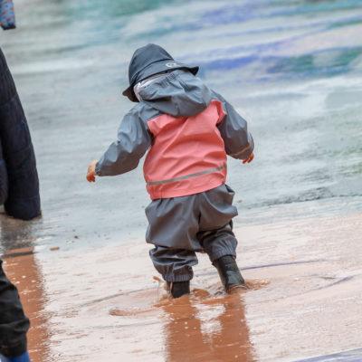 Kind mit Gummistiefeln in tiefer Pfütze