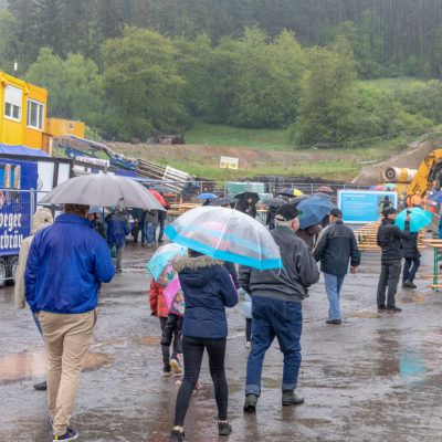 Menschen mit Regenschirmen gehen über die Baustelle