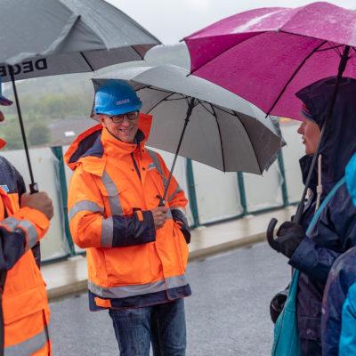 DEGES-Mitarbeiter mit Regenschirm im Gespräch mit Besuchern