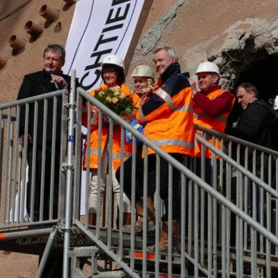 Redner und Arbeiter auf Podest vor Tunneldurchstich