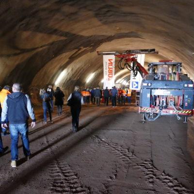 Besucher besichtigen den Tunnel, im Hintergrund Baumaschine