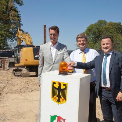 Drei Offizielle drücken den Buzzer zum Baubeginn
