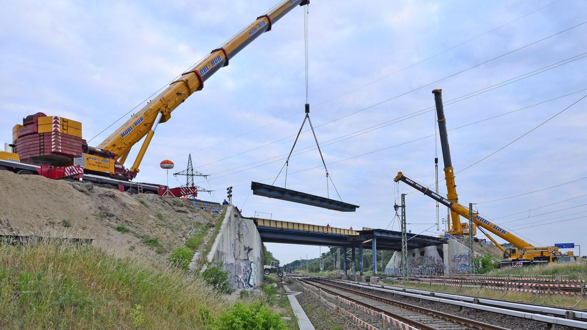 Ein großer Autokran trägt ein Stück der Brücke
