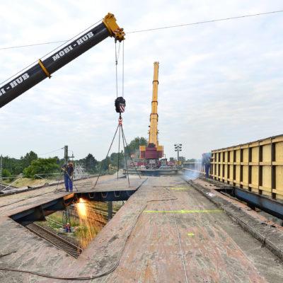 Ein Autokram hebt ein Stück der Brücke raus
