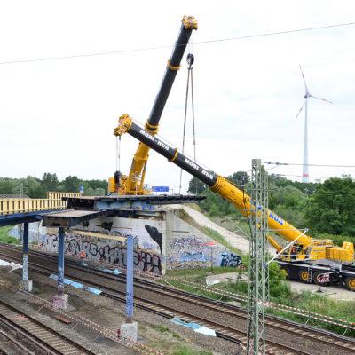 Zwei Autokräne arbeiten tagsüber am Abriss der Brücke