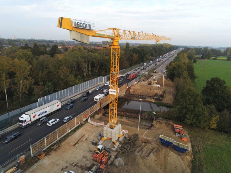 Luftbild des Brückbauwerks BW3420 über die Ochtum, im Vordergrund großer Baukran und Baustellen, Verkehr auf dem freigegeben Teil