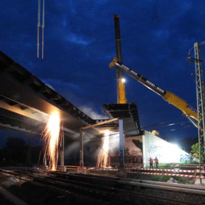 Zwei Autokräne arbeiten nachts am Abriss der Brücke