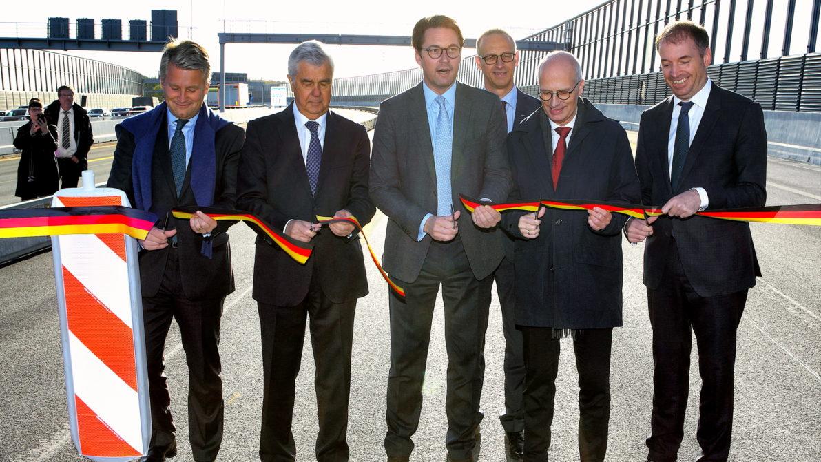 Politiker durchschneiden das Band zur Eröffnung der Brücke