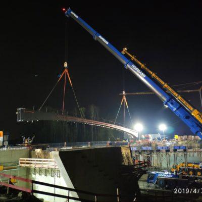 Die Brückenteile werden mithilfe eines Krans eingehoben.