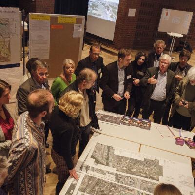 Teilnehmer der Planungswerkstatt betrachten Baupläne