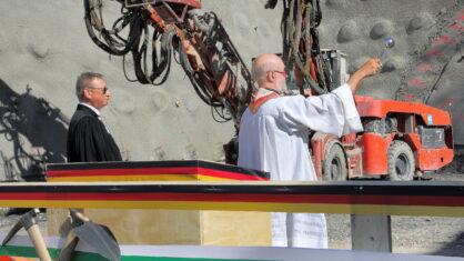 Zwei Pfarrer segnen Tunnelportal und Maschinen