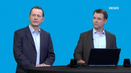2 Menschen in Anzügen in einem virtuellen Studio an einem Stehtisch mit Laptop