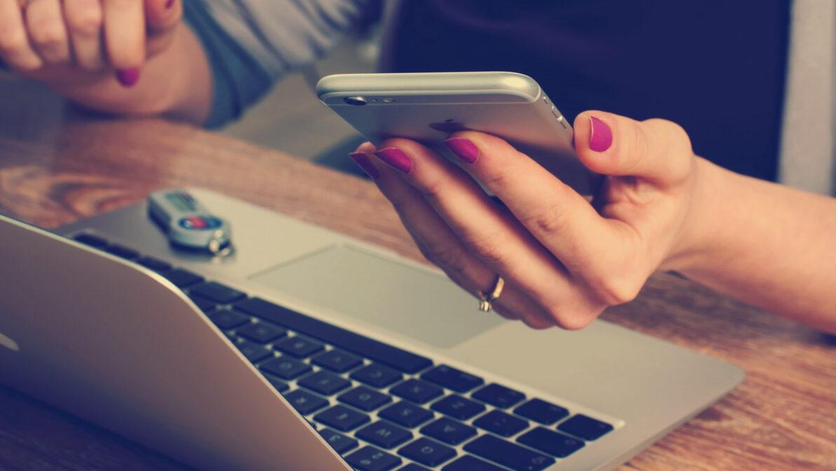 Frauenhand mit rot lackierten Nägeln sitzt am Schreibtisch mit Laptop, sie hält ein Handy in der Hand
