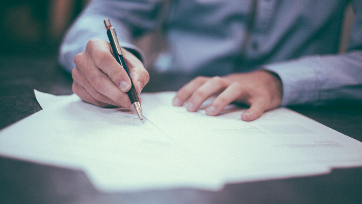 Zwei Hände, eine mit Stift - darunter Papiere