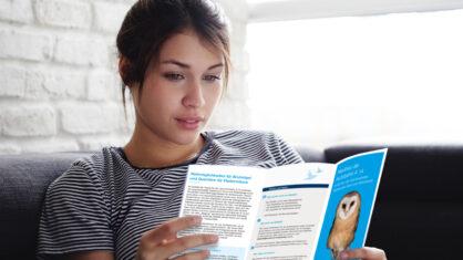 Frau liest Informationsflyer